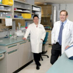 TACTICAL TECH: Dr. Richard Terek, right, chief of musculoskeletal surgery at Rhode Island Hospital, and Qian Chen, director of the hospital's Center for Biomedical Research Excellence in Skeletal Health and Repair, have developed nanoparticles to deliver medicine to limit the growth of bone cancer tumors. / PBN PHOTO/MIKE SKORSKI