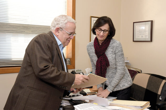 TAX GUIDES: Anthony Scorpio speaks with Judith Giannini at Mullen Scorpio & Cerilli in Providence. The certified public accountants help small businesses apply new tax laws, such as the Qualified Income Business Deduction. / PBN PHOTO/MIKE SKORSKI