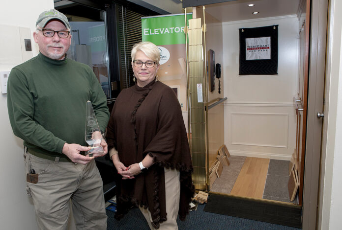 """IN DEMAND: Bill and Linda Bohmbach, owners of Home Healthsmith in Portsmouth, stand in front of a demo residential elevator holding the Prism award they received in 2019 for """"Most Creative/Unique Use of Space"""" for their residential glass elevator in Boston. / PBN PHOTO/KATE WHITNEY LUCEY"""