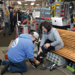 PROPER FIT: Tom Crowley, manager at The Ski Shop Plus in North Smithfield, helps Rosemary Stein of Smithfield get fitted for boots. Beyond skis and snowboards, available for rent or purchase, the shop offers a variety of accessories and clothing, including winter jackets and goggles. / PBN PHOTO/MIKE SKORSKI
