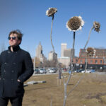 "STAYING PUT: Adam Anderson, owner of landscape architecture firm Design Under Sky and a Wavemaker fellow, stands near the remnants of his ""10,000 Suns"" sunflower installation in Providence. Anderson is still paying off his student loans and says the Wavemaker program is one of the factors that kept him in Rhode Island.  / PBN PHOTO/MIKE SKORSKI"