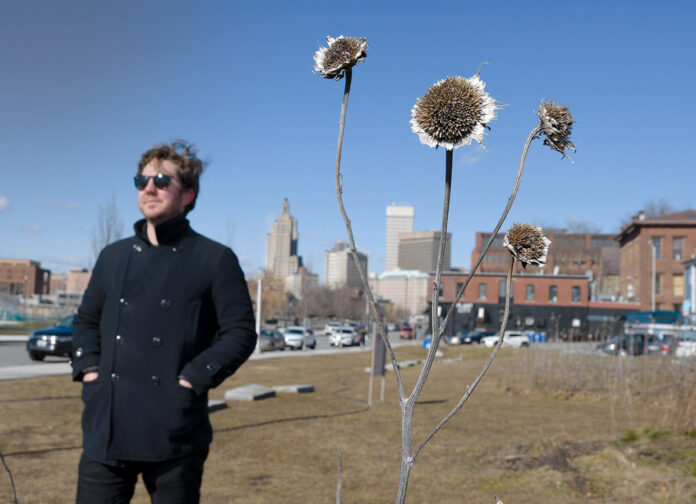 """STAYING PUT: Adam Anderson, owner of landscape architecture firm Design Under Sky and a Wavemaker fellow, stands near the remnants of his """"10,000 Suns"""" sunflower installation in Providence. Anderson is still paying off his student loans and says the Wavemaker program is one of the factors that kept him in Rhode Island.  / PBN PHOTO/MIKE SKORSKI"""