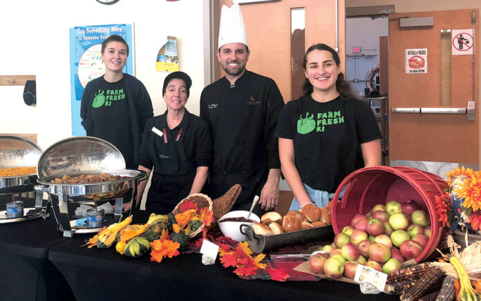 FARM TO SCHOOL: Farm Fresh Rhode Island's AmeriCorps VISTA members Rose Serra, right, and Liesl Miller, left, assist Chartwell's executive chef Steven Dafonseca and his assistant at Pocasset Elementary School in Tiverton, as they serve a harvest lunch made with locally sourced ingredients, including apples from Steere Orchard in Smithfield. / COURTESY FARM FRESH RHODE ISLAND