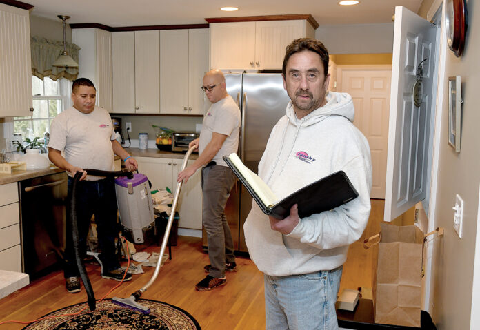 SWEEPING CHANGE: Shawn Lynch, right, owner of second-generation family business Lynch's Cleaning & Restoration Service, with Miguel Lopez, left, and Carlos Pereira cleaning smoke damage at a house on Maplewood Drive in East Greenwich. / PBN PHOTOMIKE SKORSKI