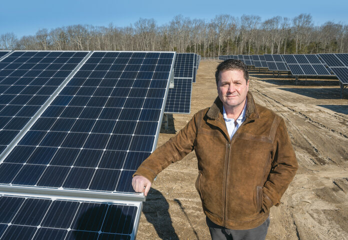 GETTING HEATED: Green Development CEO Mark DePasquale is pictured at a solar array in West Greenwich, one of several the company has built across the state. The renewable energy developer has faced opposition from towns and environmentalists due to clear-cutting of forests required for its projects. / PBN PHOTO/DAVE HANSEN