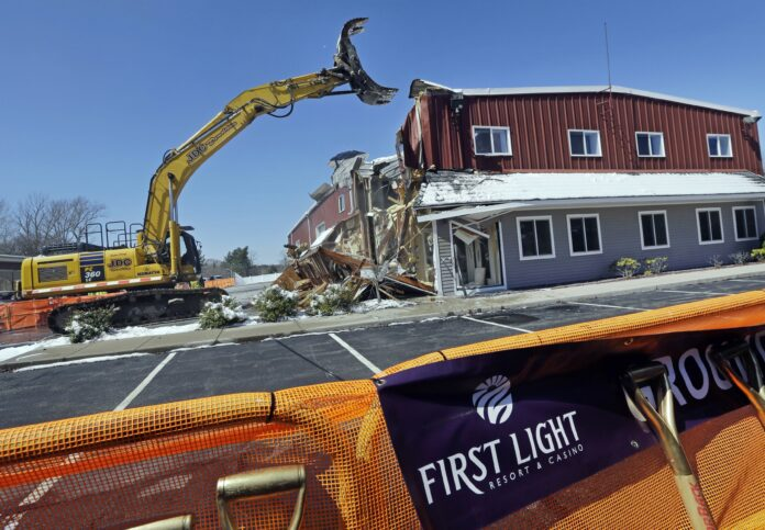 AN EXCAVATOR demolishes a building during an official groundbreaking in Taunton,, where the Mashpee Wampanoag tribe was to build the First Light Resort & Casino. The project was halted shortly afterward when a group of residents sued, arguing the federal government couldn't take the land into trust for the tribe. / AP FILE PHOTO/ELISE AMENDOLA