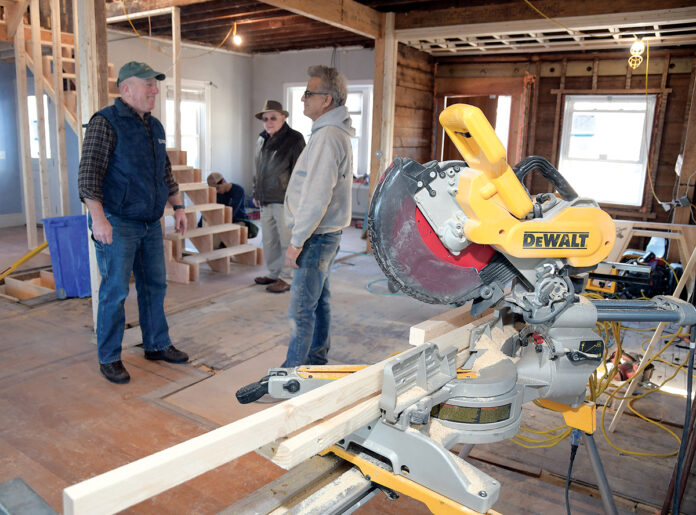 CONSTRUCTION DISCUSSION: Dave Caldwell, left, co-owner of Caldwell & Johnson Inc., talks with employee Rob Ball about the progress on a home rebuild in Cranston recently. In the background, standing, is company co-founder Dave Caldwell Sr.  / PBN PHOTO/MIKE SKORSKI