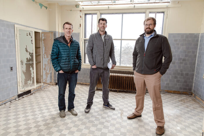 REBUILD READY: From left, Mark Van Noppen, CEO of RCG Armory LLC, architect Jack Ryan and Seth Zeren, principal of RCG Armory, stand in the room of a former nursing home at 31 Parade St. in Providence. Armory purchased the building a few years ago and will use Rebuild Rhode Island tax credits to turn it into 12 apartments. / PBN PHOTO/RUPERT WHITELEY