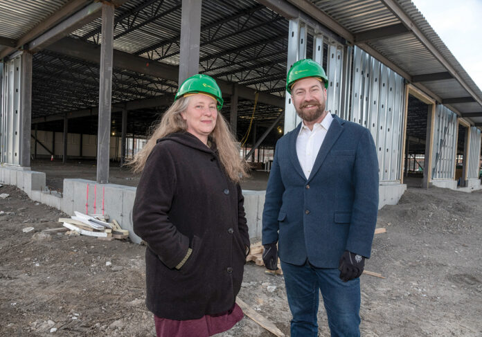 PLANTING THE SEEDS: Sheri Griffin and Jesse Rye, co-executive directors of Farm Fresh RI, stand in front of the steel framework for the organization's brand-new 60,000-square-foot Food Hub facility in the Woonasquatucket River Valley that will be completed in the fall of 2020. / PBN PHOTO/MIKE SALERNO
