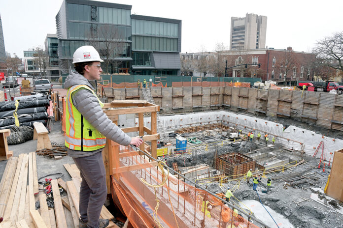 WATCHFUL EYE: A worker from Shawmut Design and Construction oversees the building of the new Brown University Performing Arts Center on College Hill in Providence in December. / PBN FILE PHOTO/MIKE SKORSKI