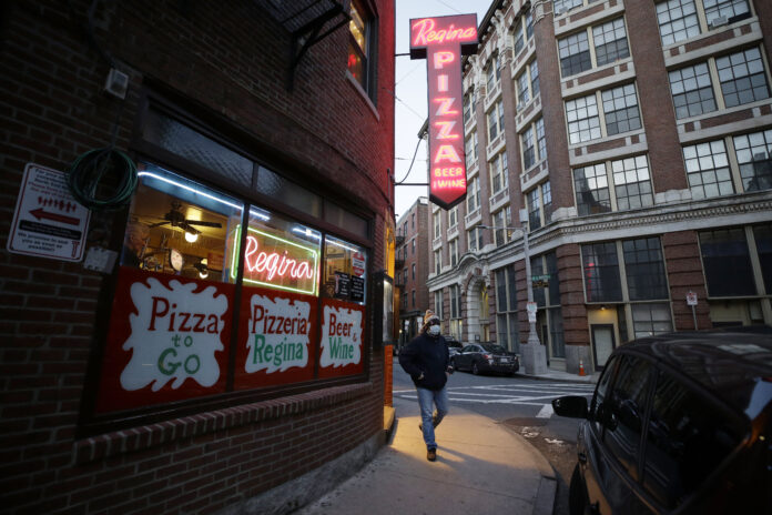 A PATRON walks near an entrance to a pizza restaurant, in Boston's North End neighborhood. Gov. Charlie Baker announced a $10 million small business recovery loan fund to help companies struggling because of efforts to slow the coronavirus pandemic. / AP FILE PHOTO/STEVEN SENNE
