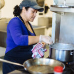 CHEF ROSA Muñoz, who works for Hope & Main member entity Savory Fare, prepares a meal in one of Hope & Main's kitchens. Hope & Main is launching next week its new Nourishing Our Neighbors program to provide free meals to seniors and needy families on the East Bay during the COVID-19 pandemic. / COURTESY RUPERT WHITELEY