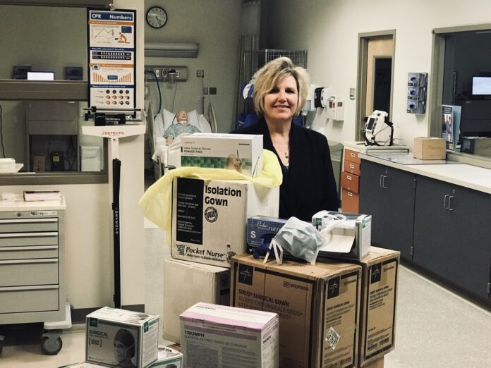 NEW ENGLAND INSTITUTE of Technology Director of Nursing and Interim Assistant Provost of Health Services Darlene Noret stands with medical supplies the school will donate Tuesday to Care New England to help with the COVID-19 pandemic. / COURTESY NEW ENGLAND INSTITUTE OF TECHNOLOGY