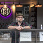 ADAPTING: Liam Maloney is a tasting room manager at The Industrious Spirit Co. The Providence company is offering free hand sanitizer it makes from the byproduct of vodka manufacturing. / PBN FILE PHOTO/MICHAEL SALERNO