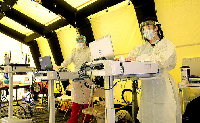 FRONT LINES: Health workers type on laptops inside a COVID-19 patient tent set up outside the emergency department at Rhode Island Hospital in ­Providence. / COURTESY LIFESPAN CORP.