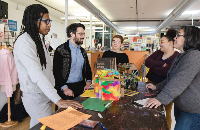 ART SUPPLIERS: New Urban Arts staff members converse at their studio in Providence. From left are Kevin Harper, operations coordinator; Daniel Schleifer, executive director; Addy Scheutz, resident arts mentor; Charmaine Porter, development associate; and Jeannie Castillo Lapierre, business manager. / PBN PHOTO/RUPERT WHITELEY