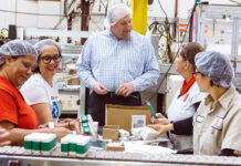HELP WANTED: Bradford Soap Works Inc. in West Warwick is one of numerous Rhode Island companies hiring even though the economy has hit the skids during the corona­virus pandemic. In this 2018 file photo, CEO and President Stuart Benton works on the packing floor with Bradford employees. / PBN FILE PHOTO/RUPERT WHITELEY