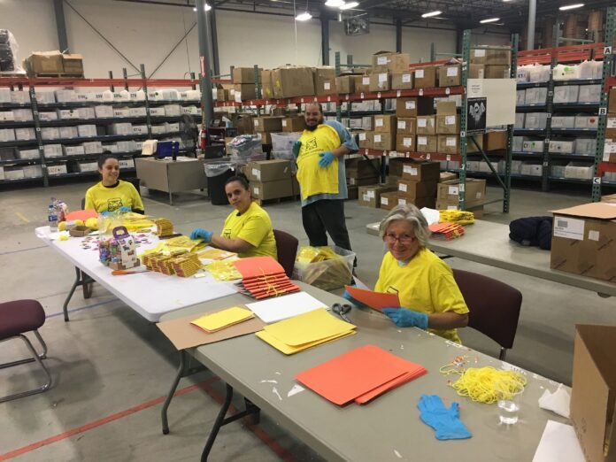 IVORY ELLA LLC employees, from left, Claritza Gonzales, Yasmin Ramos, Nelson Vasquez and Annette LaPietra, help build activity kits for national nonprofit Project Sunshine, which will be distributed to pediatric patients currently hospitalized. / COURTESY IVORY ELLA LLC
