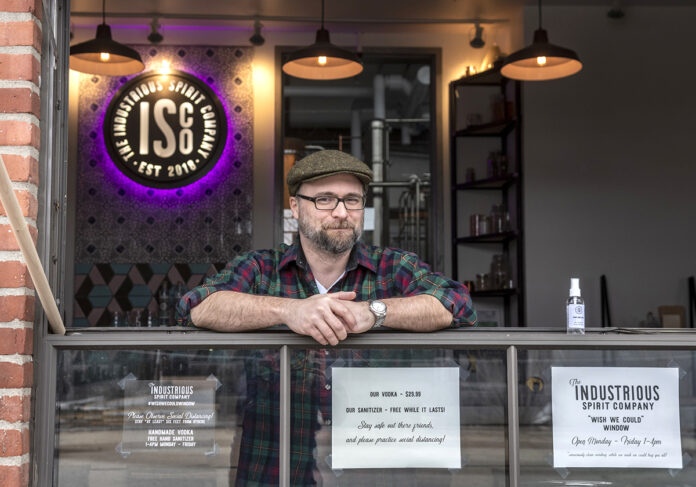 "FREE SANITIZER: Liam Maloney, tasting room manager at The Industrious Spirit Co. in Providence, stands at the company's ""drive-up"" window, where it is offering people free bottles of hand sanitizer that it makes using the byproduct of its vodka manufacturing. / PBN PHOTO/MICHAEL SALERNO"