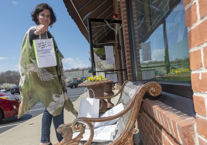 CUSTOMER-FOCUSED: Jennifer Massotti, general manager of Barrington Books in Barrington, holds up a bag with a thank-you note, which she wrote for all curbside-pickup orders. The small business was able to secure flexibility on rent payments from the landlords for both of its locations, in Barrington and Cranston. / PBN PHOTO/MICHAEL SALERNO