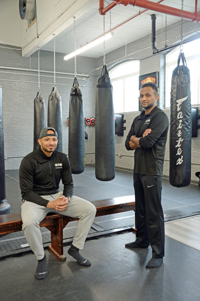 BY THE NUMBERS: Heart-rate monitors and a 3D body scan help trainer Nate Andrews, left, and Dr. Ram Yogendra, founder of ECA Wellness in Pawtucket, assess clients' fitness needs. / PBN PHOTO/ELIZABETH GRAHAM