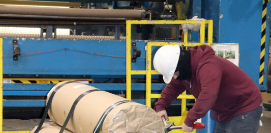 THAT'S A WRAP: Cooley Group employee Jonathan Rosado Morales packages finished product, an environmental protection barrier for the U.S. military. Despite a shortage of raw material, Cooley has maintained its shipping schedules. / COURTESY COOLEY GROUP