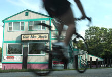 STAYING SAFE: A new PBN survey found many Rhode Islanders won't feel safe around large groups of people until next year. For businesses that rely on tourism, that might mean a renewed focus on family activities this summer, including bike tours. Above, a cyclist passes Your Bike Shop in Warren. / PBN FILE PHOTO/RYAN T. CONATY