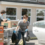 LOADING UP: Ric Wild, executive director at the Good Neighbors Inc. food pantry in East Providence, loads bags of food into a vehicle while volunteer Elaine Fredrick fills boxes. / PBN PHOTO/TRACY JENKINS