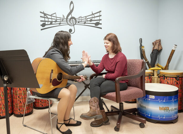DUAL HARMONY: Nicole O'Malley, left, is the founder and executive director of Hands in Harmony, which uses musical therapy to help individuals with complex medical conditions. Here, O'Malley works with longtime client Abigail Magiera, 21, of Coventry. / PBN PHOTO/DAVE HANSEN