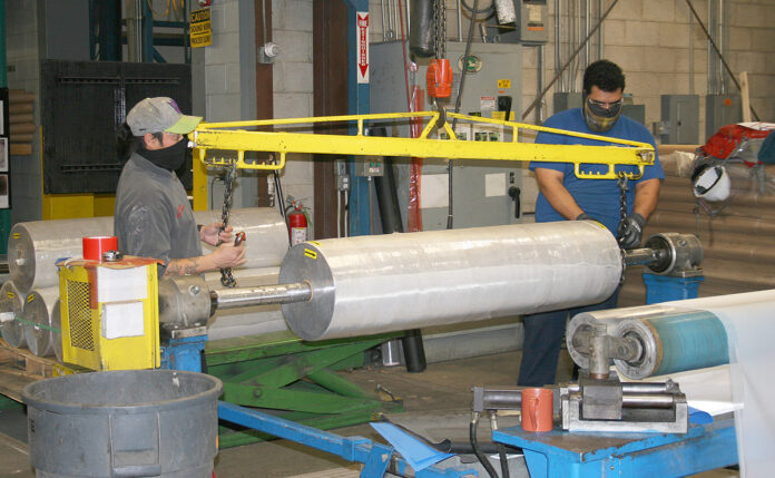 KEEPING THINGS ROLLING: Workers at Cooley Group's Pawtucket factory prepare material for shipment. The company is repurposing some of its products to create personal protection equipment for medical workers. / COURTESY COOLEY GROUP