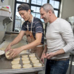 WEEKEND WARRIORS: Knead Doughnuts co-owner Adam Lastrina, right, and Bryan Tsai, production supervisor, prepare doughnuts in March. While the bakery has three locations in Rhode Island, only one remains open, serving takeout orders on the weekends only. / PBN FILE PHOTO/MICHAEL SALERNO