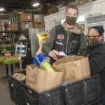 FOOD PREP: Roch's Fresh Foods Vice President Zach Roch and Michelle Rivera, curbside pickup manager, prepare orders for delivery. The grocery wholesaler is now delivering food to people who are homebound because of COVID-19. / PBN PHOTO/MICHAEL SALERNO