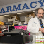COMMUNITY RESOURCE: Nicholas Shanos is the owner and head pharmacist at Suburban Pharmacy, a second-generation, family-owned pharmacy in Warwick. He is holding a bottle of his own hand sanitizer. / PBN PHOTO/MICHAEL SALERNO