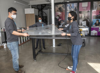 NEW DESIGN: The staff at Loft LLC, an industrial design company, has recently pivoted its work to designing and building contactless COVID-19 testing trailers for use by the National Guard. From left, Scott Noh, product design; Jeanette Numbers, co-founder; Nari Shin, designer/textile specialist. In the background is David Baker, director of engineering. / PBN PHOTO/MICHAEL SALERNO