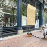 MOVING FORWARD: Domenic Merolla, a clerk at ENO Fine Wines in Providence, on June 2 cleans up shattered glass and spilled alcohol from looting at the store. / PBN PHOTO/ NANCY LAVIN
