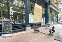 MOVING ­FORWARD: Domenic Merolla, a clerk at ENO Fine Wines in Providence, on June 2 cleans up shattered glass and spilled alcohol from looting at the store. / PBN PHOTO/ 