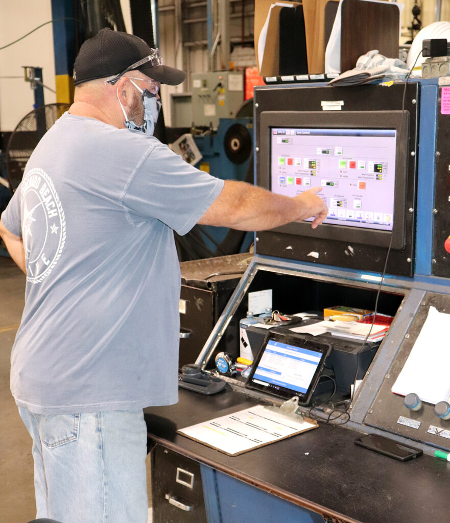 A SPECIAL TOUCH: Cooley Group team leader Arnold McLaughlin operates an extruder via a touchscreen monitor at Cooley's Pawtucket location.  / COURTESY COOLEY GROUP