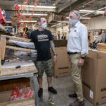 TESTED: WaterRower Inc. CEO and President Peter King, right, speaks with assembly worker Lenny Laur. The Warren manufacturer has managed two COVID-19 outbreaks among employees. / PBN FILE PHOTO/MICHAEL SALERNO
