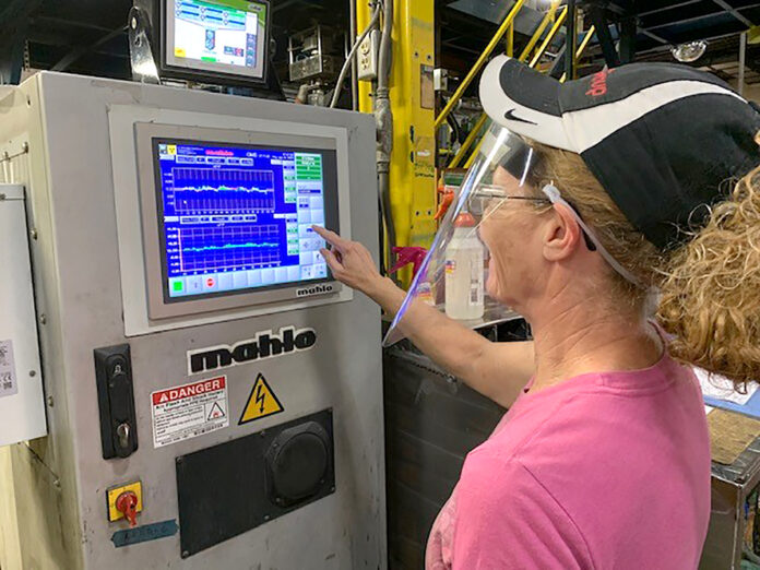 PROPERLY SHIELDED: Terri Mehaffey operates an extrusion line at the Cooley Group factory in Pawtucket. Face shields and masks can be uncomfortable for those dealing with the heat on the factory floor. / COURTESY COOLEY GROUP