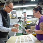 INSPECTION: Renaud Megard, CEO and president of NFI Corp. in New Bedford, inspects a face shield with Jennifer Bodnar, who works in the finishing department. / PBN PHOTO/ELIZABETH GRAHAM