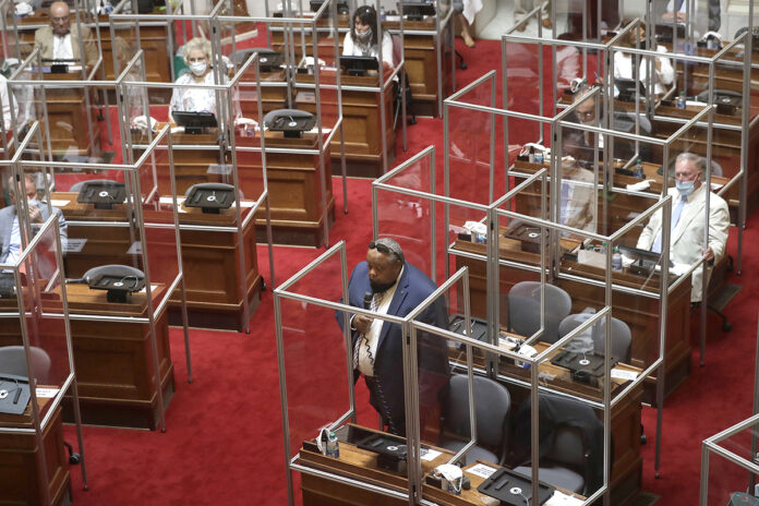 GLASSED IN: Rep. Raymond Hull, below center, D-Providence, speaks on the floor of the House chamber at the Statehouse on June 17. He and his fellow lawmakers are surrounded by plastic protective barriers because of COVID-19. / AP PHOTO/STEVEN SENNE