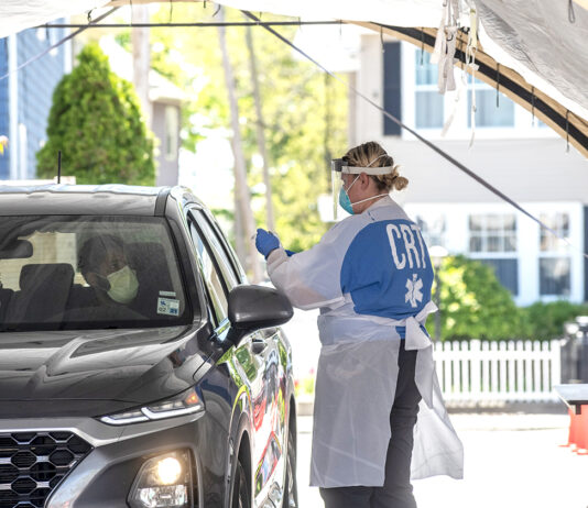COLLABORATIVE EFFORT: A staff member from Alert EMS gets a COVID-19 test sample from a drive-up patient at a mobile test site in Central Falls. Alert EMS staff handles the swabbing, CVS Health Corp. runs the machines that process the samples and the University of Rhode Island helps house the machines. / PBN PHOTO/MICHAEL SALERNO
