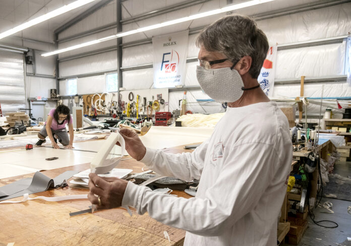BRANCHING OUT: Kinder Industries owner Phillip Kinder displays the face shield and mask that his company recently started producing for health care workers and commercial orders. In the background, head seamstress Misuk Toppa cuts strips for enclosure panels that are going to Regata Place in Newport. / PBN PHOTO/MICHAEL SALERNO