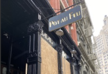 BOB BURKE, owner of Pot Au Feu in downtown Providence, covered his restaurant in plywood on Friday ahead of planned demonstrations. / PBN FILE PHOTO/NANCY LAVIN