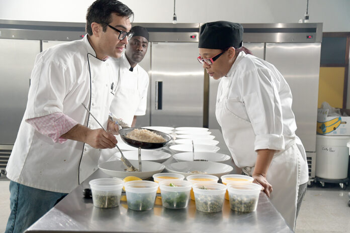 "NOT CONVINCED: Joshua Riazi, left, manager at Genesis Center, leads a culinary class in February. Riazi isn't sold on the idea of forming an association to serve as a ""chamber of commerce"" for the Rhode Island nonprofit sector.  / PBN PHOTO/MIKE SKORSKI"