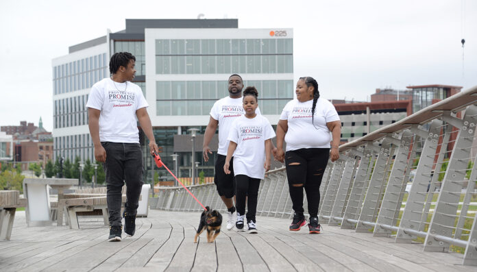 ENROLLED: Torrell Mola, right, has enrolled her children in Providence Promise, a nonprofit focused on providing support for students to seek higher education. From left, Mola's son Keyon; husband, Bruyere; and daughter Iliyah walk Bella, the family dog, along the Providence Pedestrian Bridge. / PBN PHOTO/ELIZABETH GRAHAM