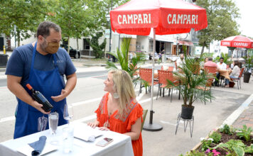 BOTTLE OF VINO: Armando Bisceglia, owner of Bacco Vino & Contorni on Providence's Federal Hill, serves wine to Sarah Long of Swansea on a Friday night. On Fridays and Saturdays, Atwells Avenue is closed to vehicle traffic so restaurateurs can set up tables outside along the street. / PBN PHOTO/ELIZABETH GRAHAM