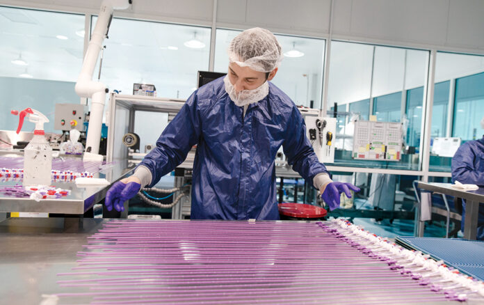 ALL LINED UP: Josh Baron, secondary ops print operator at Hitachi Cable America Inc. – High Performance Medical Solutions Division, prints peripherally inserted central catheters at the Hopkinton facility. / PBN PHOTO/RUPERT WHITELEY