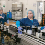 FEELING HEALTHY: Joann Stevens, left, and Angela Uricai help operate a machine at Pure Haven LLC. The Johnston-based company creates beauty products using toxin-free ingredients. / PBN PHOTO/TRACY JENKINS