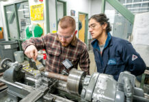 SPIN CYCLE: New England Institute of Technology Advanced Manufacturing Coordinator Todd Sposato, right, works with student Zach Carmody, 24, of Charlestown on the lathe at the Shipbuilding/Marine and Advanced Manufacturing Institute workroom at New England Tech's Warwick campus. PBN PHOTO/DAVE HANSEN